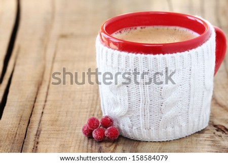 Cozy Christmas setting with a red mug of hot hot and frothy black coffee on a rustic wooden background with copy space - stock photo