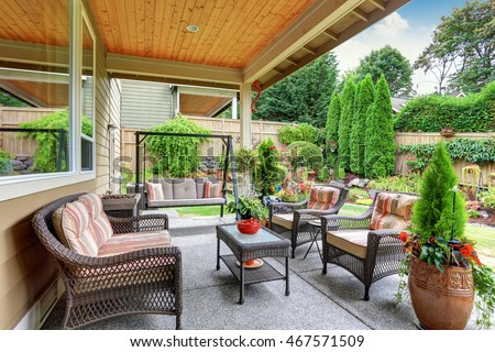 Cozy covered sitting area with wicker chairs and swing bench. Northwest, USA