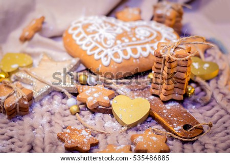 Cozy decorative scene with gingerbread heart-shaped, sugar stars cookies on a vintage rustic knitted background, decoration wooden hearts and stars, Copy space, Selective focus, toned.