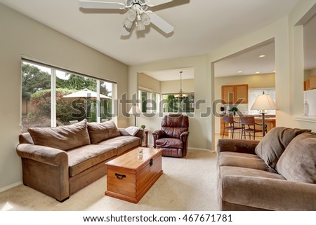 Cozy elegant family room with backyard view. furnished with brown velvet sofa set and wooden chest. Northwest, USA