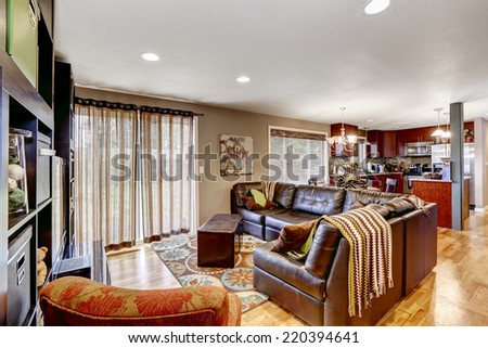 Cozy family room with leather couch bright kitchen area with burgundy cabinets - stock photo