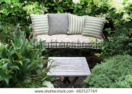 Cozy garden lounge chair with pillows, surrounded by green shrubs. Also available in vertical.