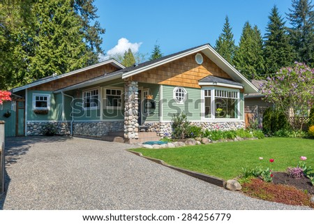 Cozy green house with beautiful landscaping on a sunny day. Home exterior. - stock photo