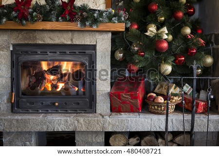 Cozy home interior of burning fireplace and colorful christmas decorations