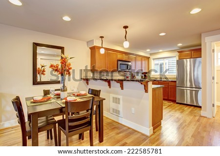 Cozy house interior. Kitchen room with wooden dining table decorated with fresh flowers - stock photo