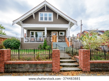 Cozy house with beautiful landscaping and brick fence. Home exterior. - stock photo