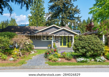 Cozy house with green door and beautiful landscaping on a sunny day with mountains in the background. Home exterior. - stock photo