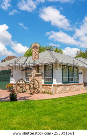 Cozy house with wagon wheel decoration. Home exterior. - stock photo
