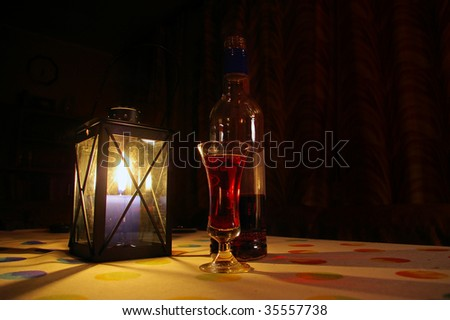 cozy indoors still-life with candle lantern and bottle and glass with red beverage - stock photo