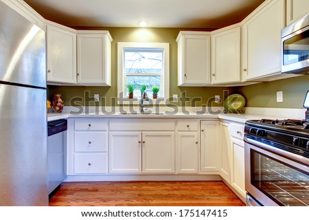 Cozy kitchen room with hardwood floor, white storage combination and soft olive wall - stock photo