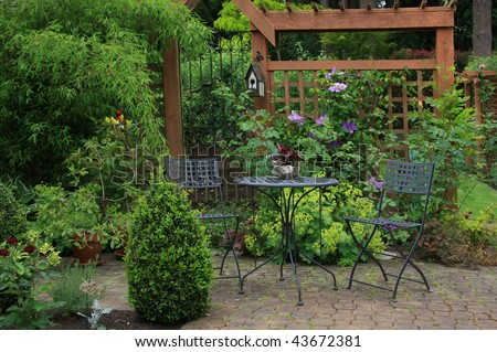 Cozy little back yard terrace with table and chair. - stock photo