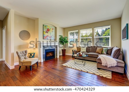 Cozy living room interior with fireplace, beige walls and hardwood floor. Northwest, USA