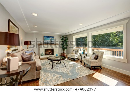 Cozy living room interior with hardwood floor and window view. Furnished with mocha colored sofa, vintage lounge Chairs and round glass top coffee table on a rug. Northwest, USA