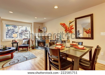 Cozy living room with dining area. Served dining table with beautiful flowers - stock photo