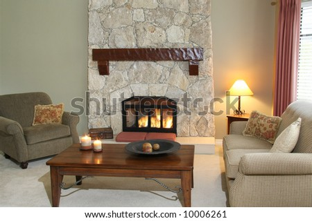 Cozy living room with fireplace turned on. - stock photo