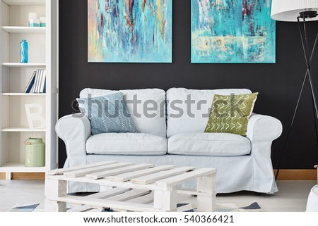 Cozy Living Room With Sofa, Cupboard, Paintings And Lamp