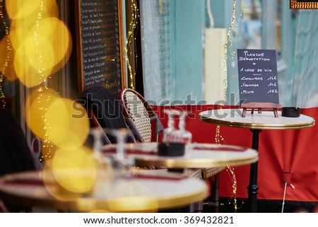 Cozy Parisian outdoor cafe with yellow lights and menu board on the table, focus on board - stock photo