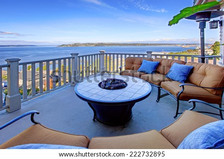 Cozy patio area with comfort settees and fire pit. Deck with Puget Sound view. Tacoma, WA - stock photo