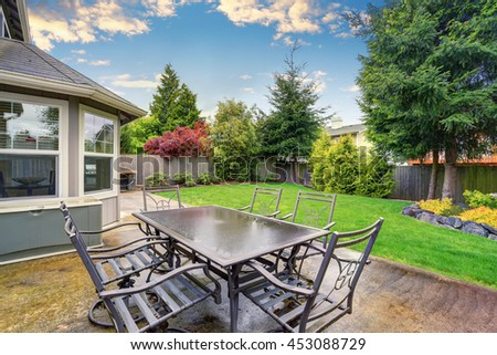 Cozy patio area with concrete floor and table set. Spacious backyard garden with green lawn. - stock photo
