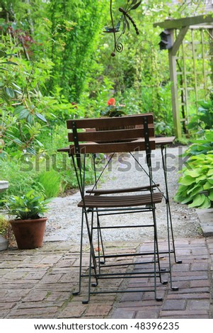 Cozy patio with table and chairs. - stock photo