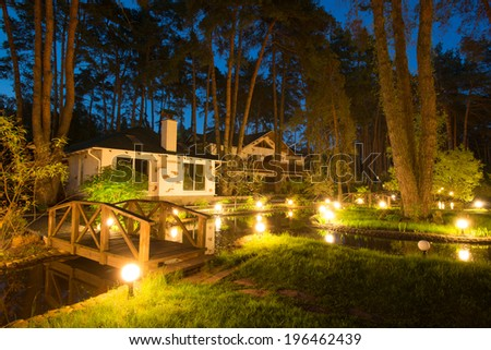 Cozy resort by the lake in the conifer forest at night - stock photo