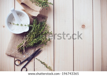 Cozy rustic home kitchen still life, dried herbs thyme, salt in white mortar, old wooden box and vintage scissors on a table background. - stock photo