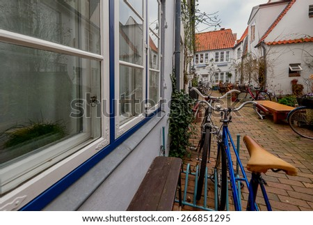 Cozy small backyard with flowers and bicycles in Lubeck. Germany - stock photo