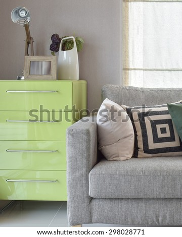 Cozy sofa with geometric pattern pillows and green sideboard in living corner - stock photo