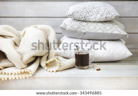 Cozy still life with coffee, pillows and plaid on the light wooden background. Close up - stock photo