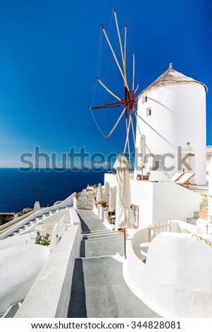 Cozy terrace ,near with romantic wind mill in Oia village at sunset. Beautiful views on mediterranean sea. Santorini (Thira) island.Cyclades.Greece.Europe. - stock photo