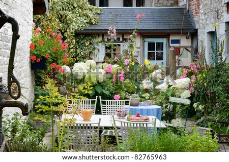 Cozy vintage backyard full of beautiful flowers - stock photo