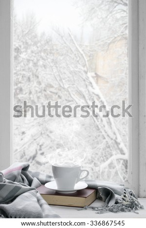 Cozy winter still life: cup of hot coffee and book with warm plaid on windowsill against snow landscape from outside. - stock photo