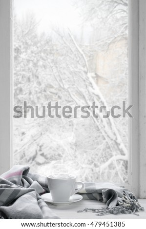 Cozy winter still life: cup of hot coffee with warm plaid on windowsill against snow landscape from outside.