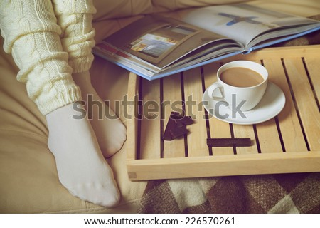 Cozy Winter: woman in warm socks with coffee and a book. Retro toning - stock photo