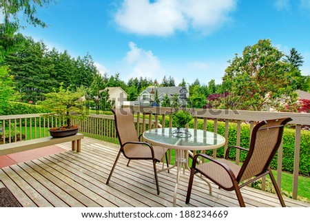 Cozy wooden deck with glass top round table and chairs - stock photo