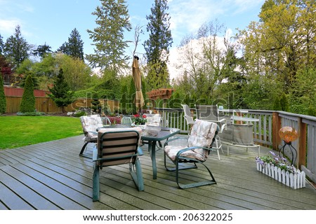 Cozy wooden deck with patio table set overlooking backyard landscape - stock photo