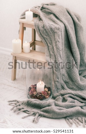 Cozy wool winter accessory. Warm sweaters candle and wood tray