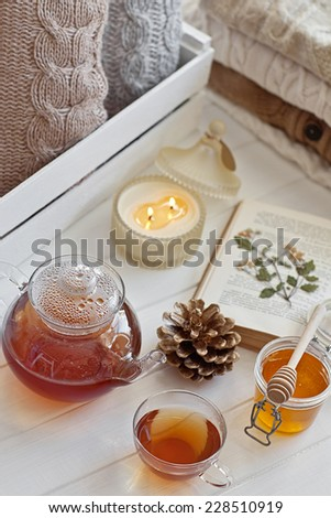Cozy wool winter accessory. Warm sweaters candle, tea and cone