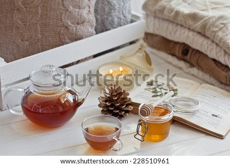 Cozy wool winter accessory. Warm sweaters candle, tea and cone - stock photo