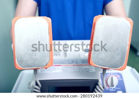 CPR device in doctors hand - stock photo