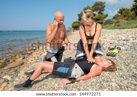 CPR training on a scuba diver on a beach - stock photo