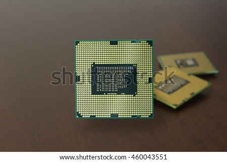 CPU (Central processing unit) microchip on dark wooden background. - stock photo