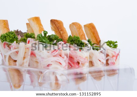 Crab and bread sticks in a plastic cone. - stock photo