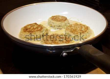 Crab Cakes frying in a ceramic skillet pan. - stock photo