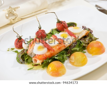 crab cooked in modern way in plate. with peach, tomato, egg and salad