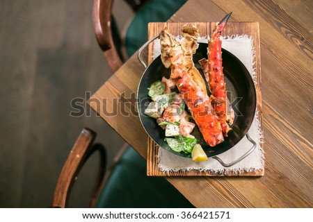 Crab phalanges with salad aside in a metal pan on a wooden table from above - stock photo