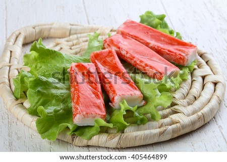 Crab sticks with salad leaves on wood background