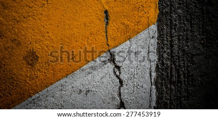 crack close up of a dark grey asphalt road divided by yellow paint - stock photo