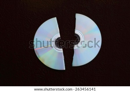 crack compact disc on black paper background in dry paint - stock photo