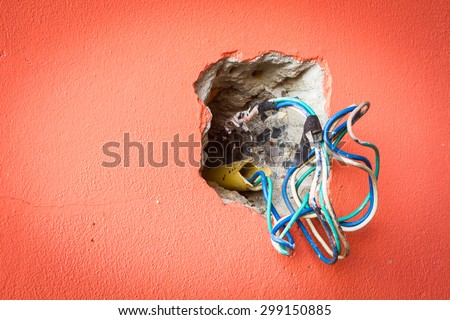 crack hole wall with electric colored wires, copyspace on the left, vignette - stock photo